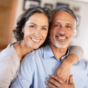 a mature couple smiling with dental implants